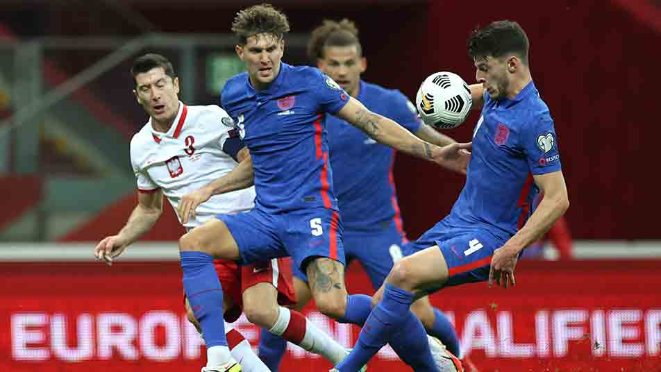 John Stones and Declan Rice clear the danger under pressure from Poland striker Robert Lewandowski