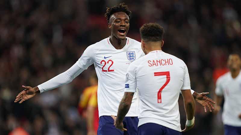 Tammy Abraham of England celebrates scoring a goal with Sancho to make the score 7-0
